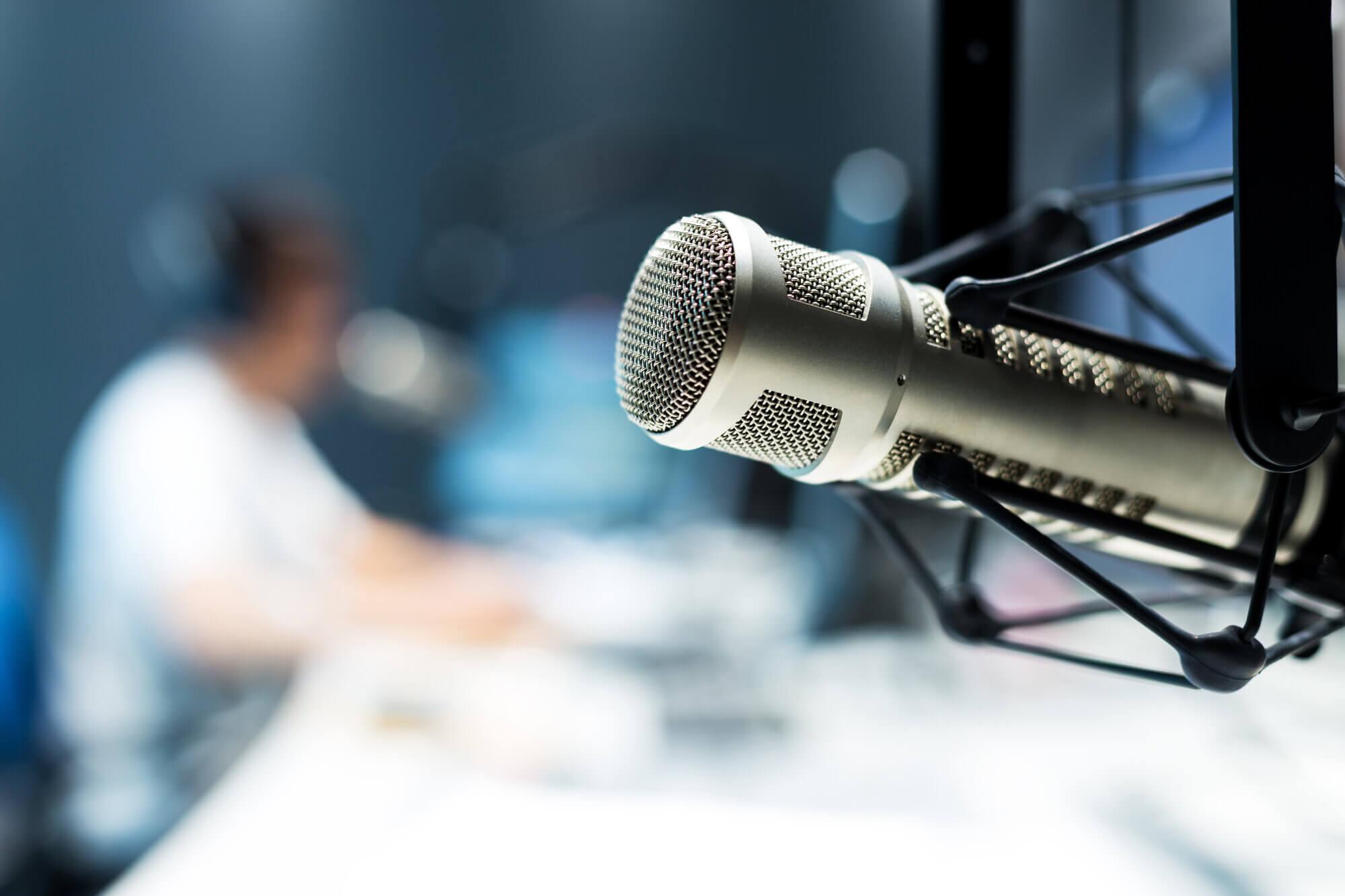young man dj works in modern broadcast studio
